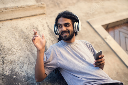 Casual young hipster with dreadlocks listening music at street and casual young hipster with dreadlocks listening music at street and looking aside greeting someone m4hsunfo