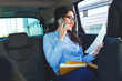 Beautiful young business woman sitting in the car looking at her planner and talking at phone.