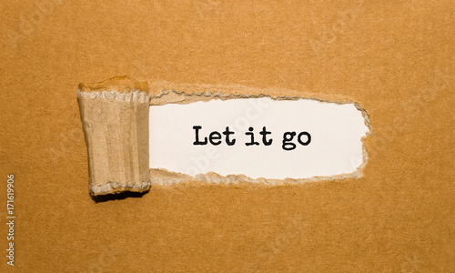 Photo  The text Let it go appearing behind torn brown paper