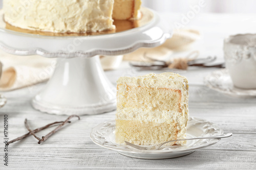 Slice of delicious vanilla cake on wooden table Canvas Print