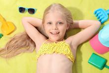 Cute Little Girl Sunbathing On Beach