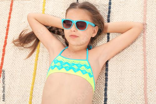 Cute little girl sunbathing on beach Wallpaper Mural