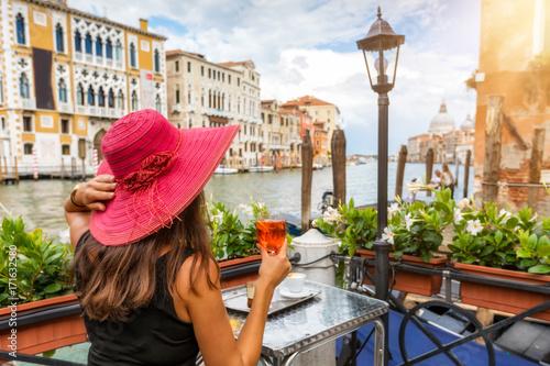 Photo Touristin sitzt am Canale Grande in Venedig, Italien, und genießt einen Aperitif