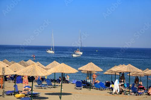 Fototapeta Parasole i leżaki na plaży wzdłuż morza. obraz