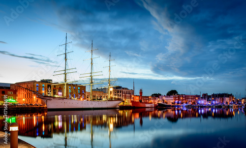 Fotografie, Obraz DUNKERQUE, FRANCE - JULY 22, 2017: Night falling on three historic ships in front of the port museum in the bassin du commerce