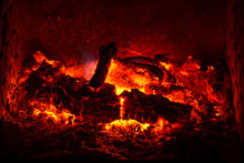 Embers With Burned Logs And Ashes In A Fireplace