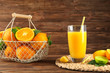 Composition with glass of fresh juice and oranges in basket on wooden table