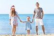Young couple with girl on beach. Christmas celebration concept