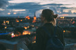 Young woman looking at evening city from skyscraper viewing platform