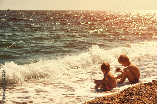 Photo brother and sister playing in the sea in backlight