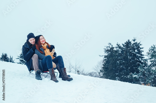 Poster Glisse hiver young couple in love enjoying a winter vacation and having fun on a snowy winter day.