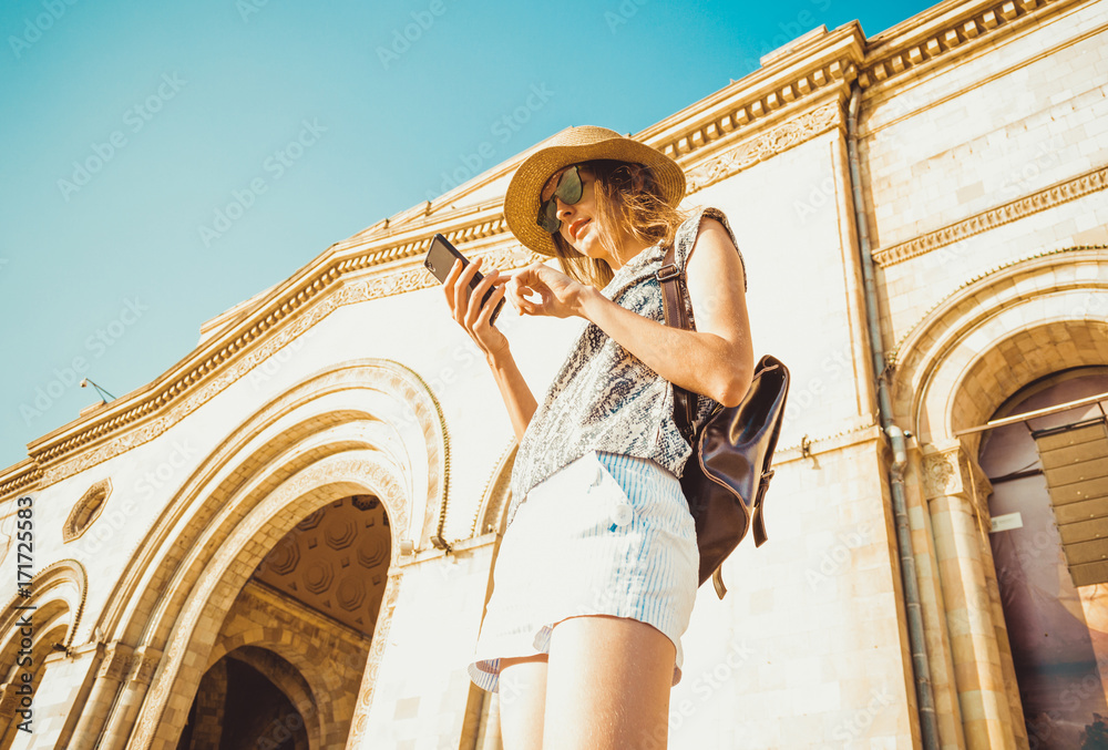 Fotografie, Tablou  Young woman tourist in hat with backpack using gps navigation on phone