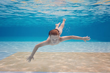 Happy Small Boy Swim Underwater, Has Fun And Dive In The Blue Transparent Water Of Clear Pool. Swimming Classes And Water Safety Education. Family Vacation, Weekend With Kids