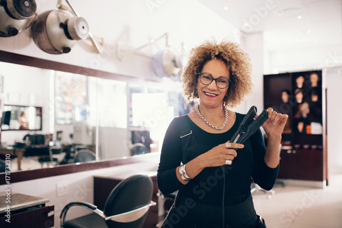 Female hairdresser at the salon holding a hair straightener