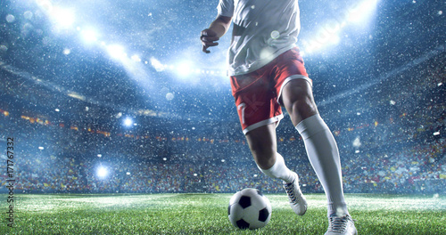 Obraz na plátně  Soccer player kicks the ball on the soccer stadium