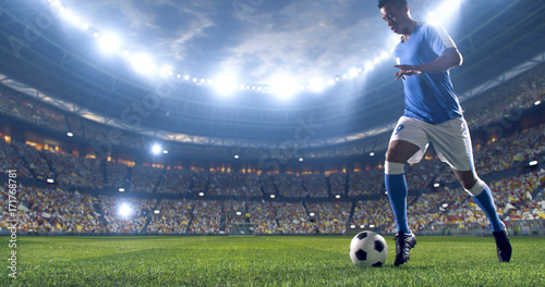 Soccer player kicks the ball on the soccer stadium Canvas Print