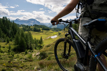 Young Adult Active Man On Mountain Wearing Bike Helmet And Backpack Looking At Scenic Panorama Holding Electric Bike In Sunny Summer Day Outdoor.