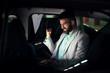 Elegant modern businessman with laptop on the back seat celebrating job success.