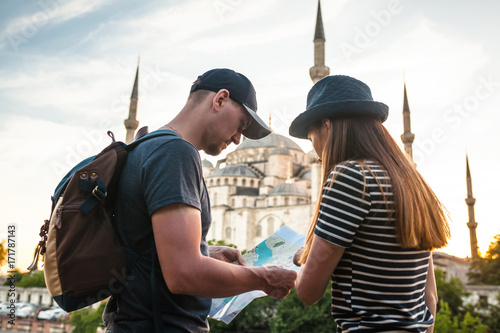 Foto  A couple of tourists a young man and a pretty woman look at the map next to the world-famous Blue Mosque also called Sultanahmet in Istanbul, Turkey