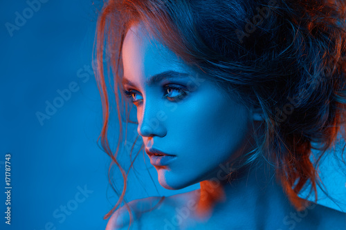 Foto op Plexiglas Kapsalon Portrait of beautiful girl in blue light and red light close up with hairstyle