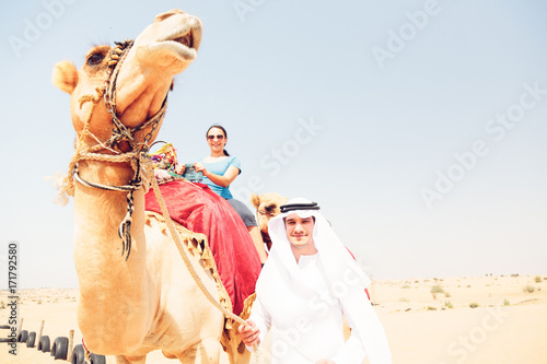Fotografija  Arabian Man And Tourist Riding A Camel