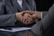 Businesspeople or lawyers shaking hands at meeting. Close-up of human hands at work. Signing contract concept. Low key lighting