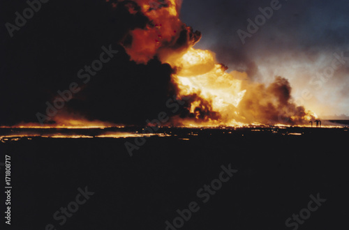 Massive oil well fire in field with oil slick, Kuwait Wallpaper Mural