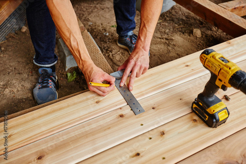 Fotografia  man drilling and measuring wood for deck