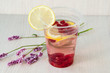 Still life: water with lemon and raspberries, wild flowers