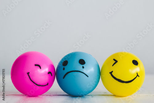 Fotografia Emotions balls: Happy smiley face pink and yellow ball and depress sadness ball