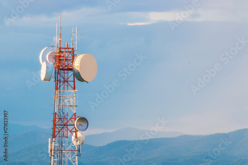 telecommunication tower with mountain range background with warm sunset light casting on clouds