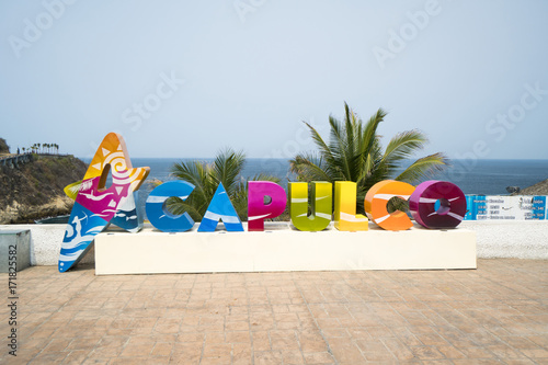 Fototapeta Colorful Acapulco inscription sign with bright colorful letters on a shoreline i