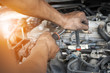 Hands of mechanic working in auto repair shop with sunlight