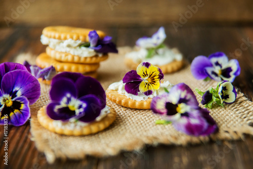 Fotografie, Obraz  Sandwich with herb and edible flowers butter on wooden background, healthy food