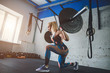 Fit young woman lifting barbells looking focused, working out in gym