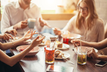 Leisure And Food Concept - Friends Having Dinner And Eating At Restaurant