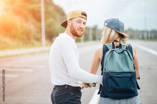 Fototapeta girl on bike, guy runs. boy teaches girl to ride a bike. Morning Meadow. obraz na płótnie