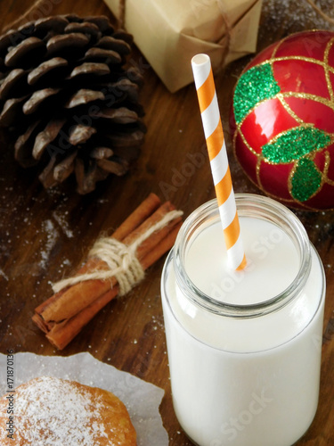 Foto op Plexiglas Milkshake Milk in a glass jar with a straw. Christmas attributes in the background. View from above