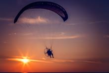Paraglider Flying At Sunset