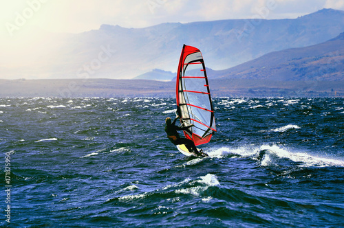 Sportman windsurfer on the lake surface.