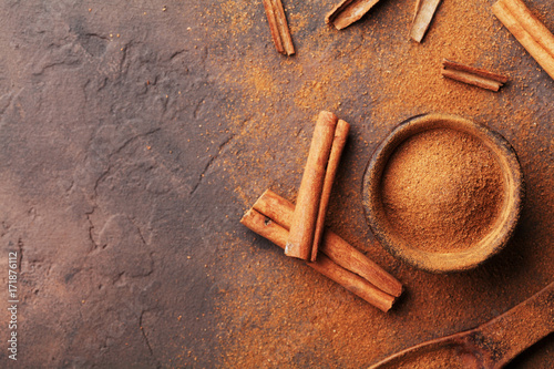 Heap of cinnamon sticks and powder on brown rustic background top view. Aromatic spices.