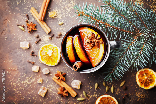 Mug of christmas mulled wine or gluhwein with spices and orange slices on rustic table top view. Traditional drink on winter holiday. Vintage toned.