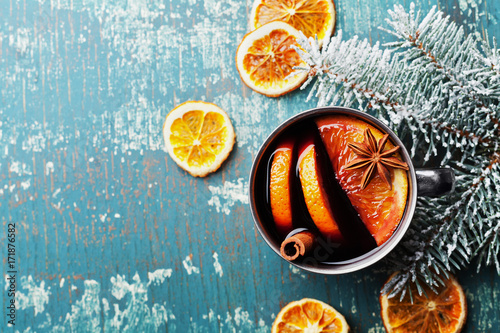 Hot christmas mulled wine or gluhwein with spices and orange slices on vintage teal table top view. Traditional drink on winter holiday.