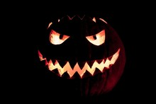 Round Halloween Pumpkin Smile With Hot Burning Fire Eyes Mouth. The Big Helloween Symbol Has A Mad Face Glowing Eyes And Also A Glow In Its Mouth And Teeth. Black Orange Nightmare Of October 31st