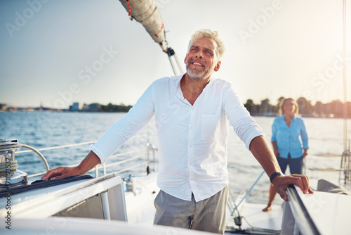 Smiling mature couple enjoying the day sailing on their boat