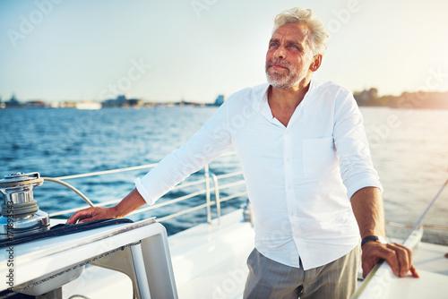 Fotografía  Mature man standing on the deck of a sailboat