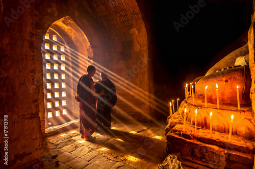 Платно Two asian Burmish monk change the robe with sun ray in pagoda at bagan, mandalay