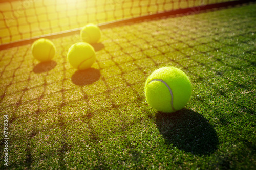 Tennis balls on grass court with sunlight