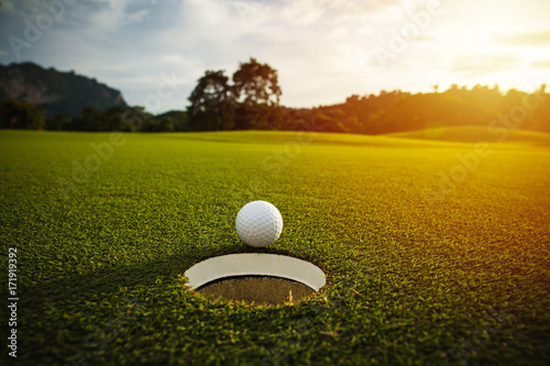 Poster Golf selective focus. white golf ball near hole on green grass good for background with sunlight and lens flare effect