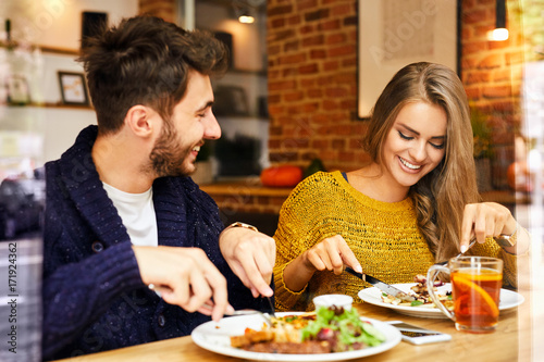 Photo Cheerful cute young couple laughing and eating lunch together in a cafeteria